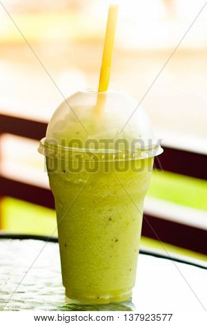 Kiwi juice in a plastic glass / Kiwi smoothie