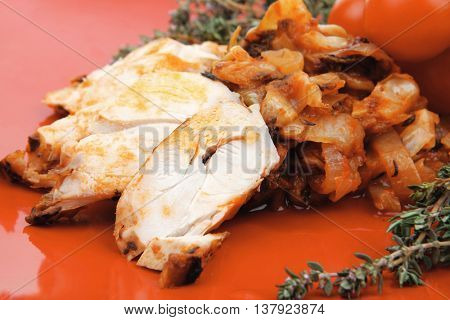 meat grilled chicken fillet with salad and tomatoes on red plate isolated over white background