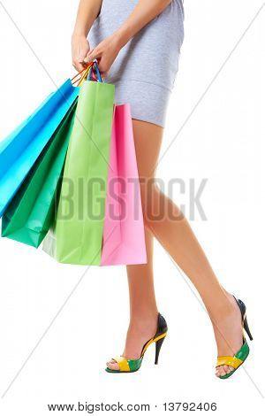 Imagem de pernas femininas magro em sapatos elegantes e paperbags em mãos no fundo branco