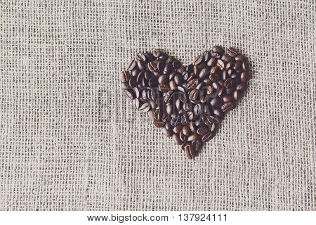 Burlap texture with coffee beans heart shape background, love symbol. Stained sack cloth canvas with copy space. Seeds at hessian textile.