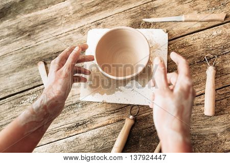Hands above clay bowl on wooden table, artisan pov. Handmade pottery, potter working at studio