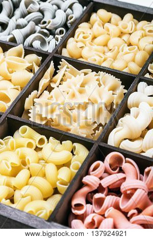 pasta assortment background. Pasta in a wooden box. Italian pasta of different colors. focus on the paste in the upper portion of the frame