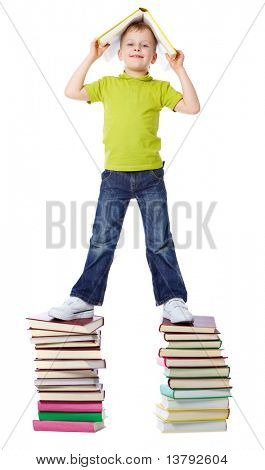 A cheerful boy standing on two heaps of books and holding a book over his head