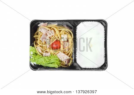 Takeaway carbonara spaghetti in a black plastic box covered with transparent plastic sheet