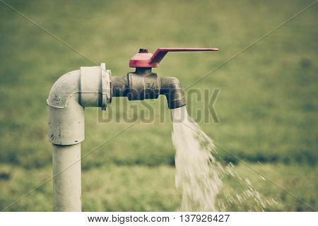 Running water from a tap with green grass background / Water consumption and usage concept