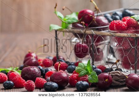 Some small glasses of fruit containing cherry, blueberry and rasberry on a wooden table