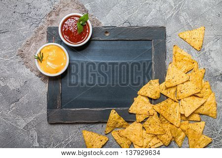 Mexican nacho with sauces and chalk board on gray background, top view, copy space