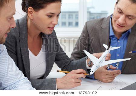 Três engenheiros olhando em um pequeno modelo de um avião
