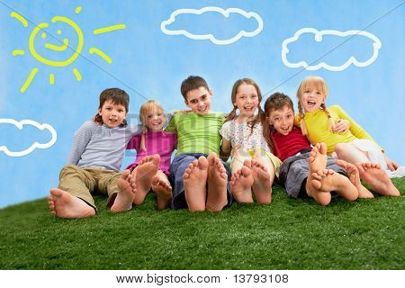 Group of happy children relaxing on the grass together