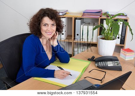 Cheerful Businesswoman Sitting At The Table In Office Writting