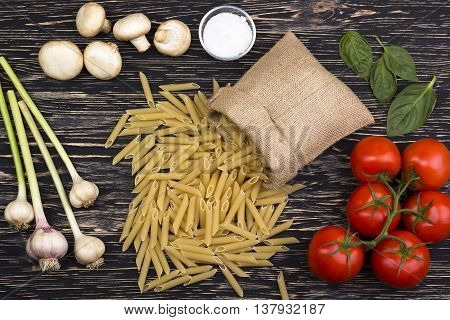 Pasta ingredients. Tomatoes, pasta, garlic basil, champignon and salt on wooden background