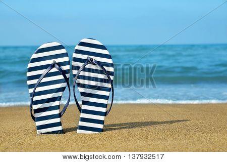 Flipflops on a sandy ocean beach. Summer vacation concept.