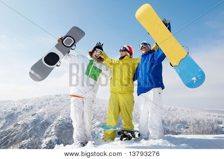 Portrait of happy three sportsmen raising their snowboards