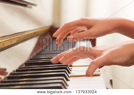 Close up of female hands playing piano with one hand on the keys the other hand floating above and about to hit the keys selective focus on the hand on the keys