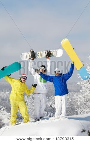 Portrait of joyful three snowboarders raising their boards