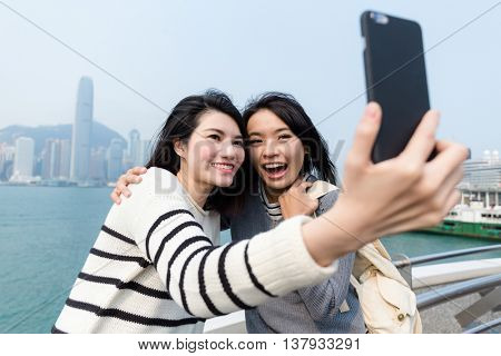 Friends taking selfie by cellphone in Hong Kong