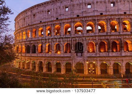 view of famous Colosseum illuminated at night in Rome, Italy