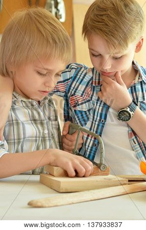 cute little boys  working with wood in  workshop