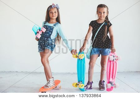 Two 7 years old children wearing cool fashion jeans clothing posing with colorful skateboard against white wall, urban style