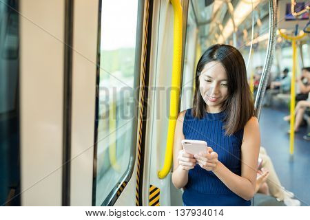 Woman sending text message inside train compartment