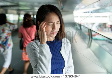 Woman feeling headache in the foot bridge