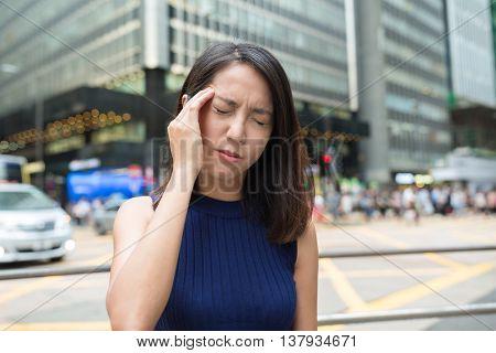 Woman feeling headache at outdoor in Hong Kong