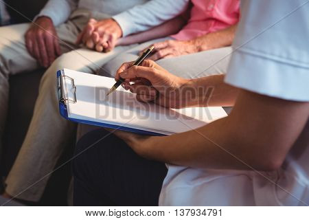 Nurse writing on clipboard in a retirement home