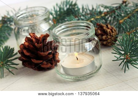 Handmade simple winter home decoration. Candle in glass jar, evergreen conifer twigs, cones. Natural festive scents.