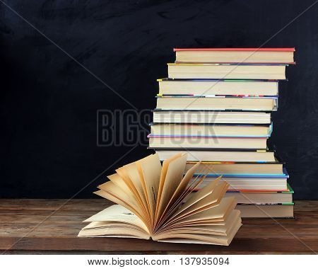 Stack of books and open book on the table amid the school blackboard. Back to school.