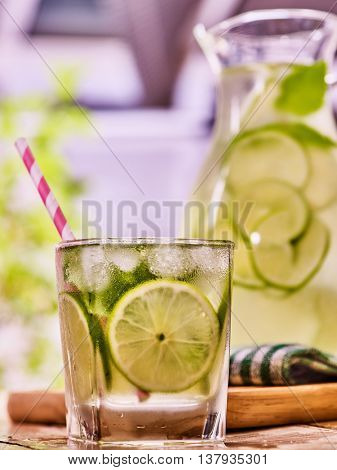 Country drink. On wooden boards is glass jug with transparent drink and lime glue bowl. A drink number seventy eight with ice cubes . Country life. Light background.