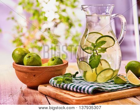 Country drink. On wooden boards is glass jug with transparent drink and lime glue bowl. Drink number seventy seven with jug and ice cubes . Country life. Light background.