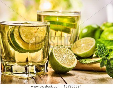 Alcohol drink. On wooden boards two glasses with alcohol green transparent drink and half lime . Drink number seventy one cocktail mojito with slice lime and mint leaf. Country life. Light background.