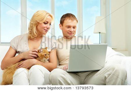 Una pareja de jóvenes sentados en el sofá y mirando la pantalla del ordenador portátil