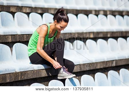 Young woman is tying a shoelace before jogging.