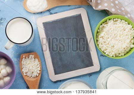 Dairy products on stone table. Sour cream, milk, cheese, yogurt and curd. Top view with blackboard for your text