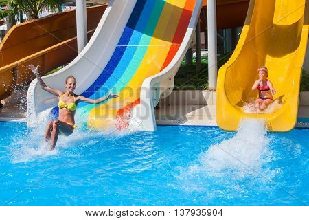 Two children sisters on water slide at aquapark shows thumb up. Summer holiday. There are two water slides in aqua park. Outdoor.