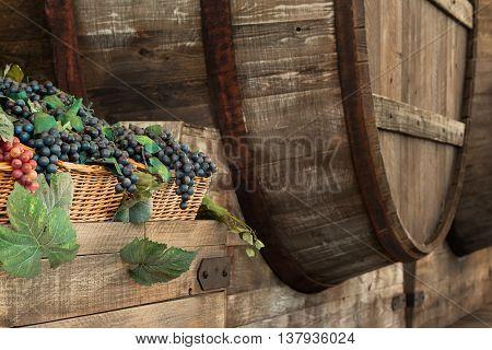 Bunch Of Colorful Grapes In Wodden Basket Near Big Barrel On Shelf