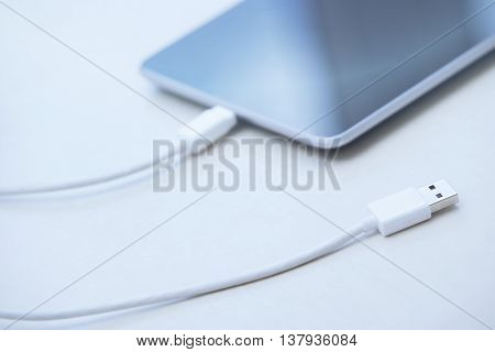 Tablet computer with USB cable laying on a table