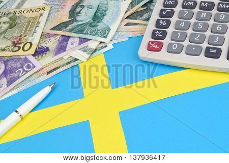 Swedish Kroner notes on a Swedish flag with a calculator and pen.