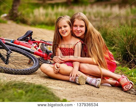 Bikes cycling children. Happy children are sitting on country road near bicycles. Cycle racing concept.