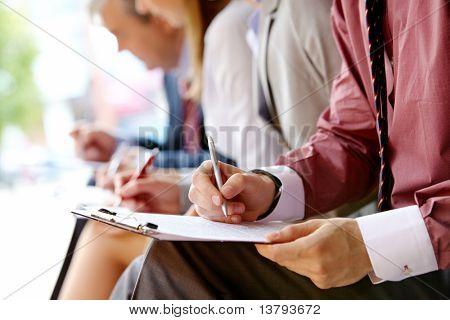 Mão humana sobre o papel, fazendo anotações no ambiente de trabalho