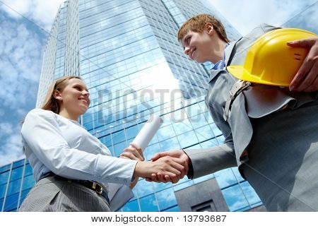Image of two businesswomen handshaking at background of modern office building