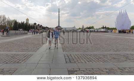 Moscow - May 6 2016: Happy young couple going along the main avenue and people walk exploring the beautiful attractions in the Victory Park May 6 2016 Moscow Russia