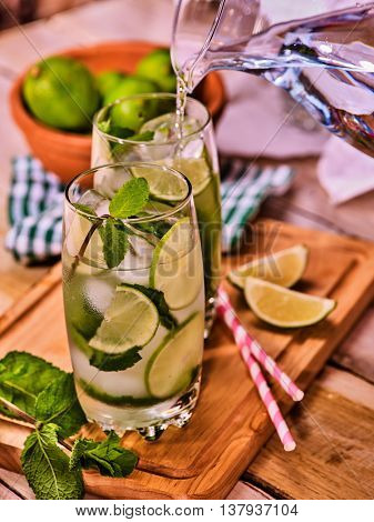 Country drink. Pouring from jug of cocktail drink on wooden boards with lime and mint . Drink number seventy three with mohito cocktail and ice cubes . Country life. Light background.