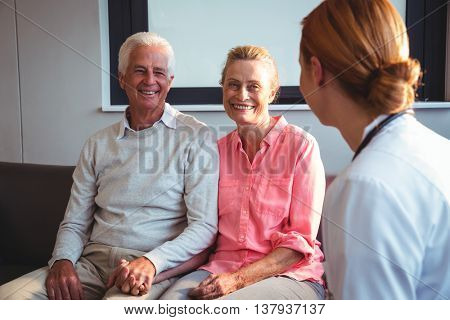 Nurse talking to senior couple in a retirement home