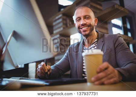 Portrait of happy creative businessman holding disposable cup while using graphics tablet