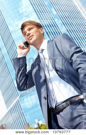 Vertical image of successful boss calling by mobile near a modern building
