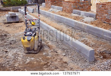 vibratory plate compactor at a construction site. small gasoline single direction plate compactor at the construction of the entrance to the building. Asphalt paving machine