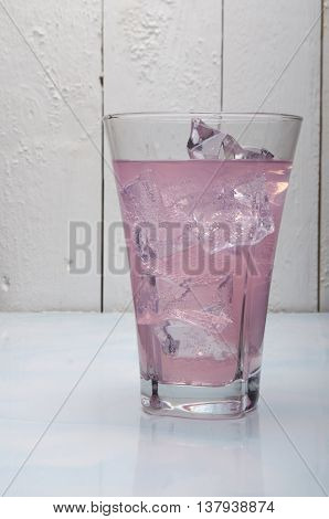 juice with ice in a glass glass on a white background