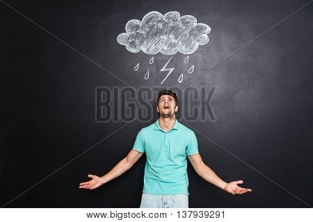 Angry young man standing with raised hands and shouting over blackboard with drawn raincloud